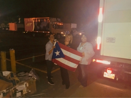 Photo: San Juan City Hospital staff at airport holding Puerto Rican flag